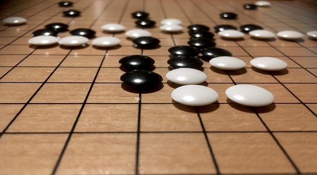 Brettspiel Go - schwarze und weisse Steine liegen auf dem Spielbrett von Go